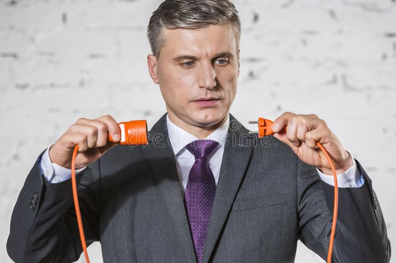 Confident mature businessman attaching red cables against white brick wall stock photos