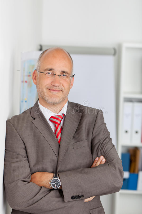 Confident Mature Businessman Leaning On Wall royalty free stock images