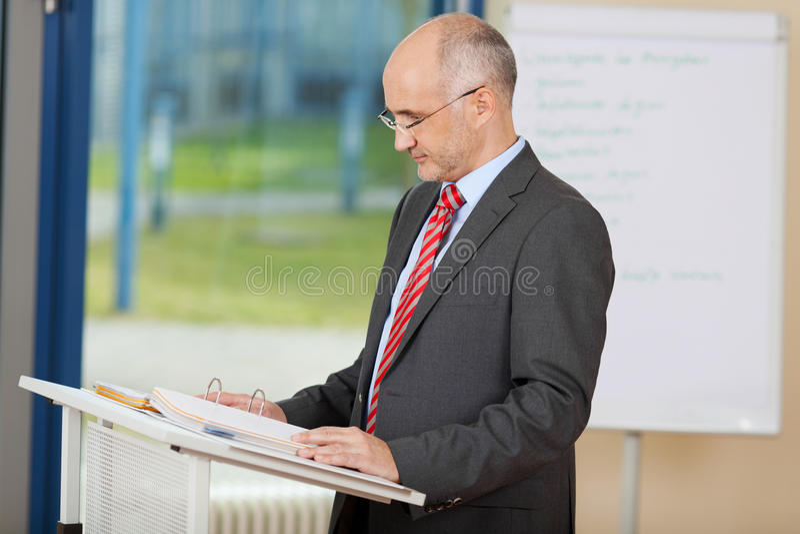 Confident Mature Businessman Reading At Podium royalty free stock image