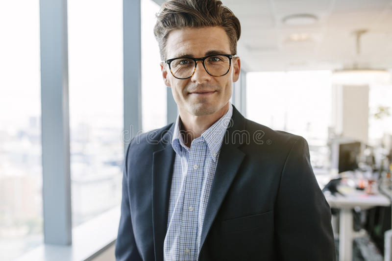 Confident mature businessman standing in office stock photography