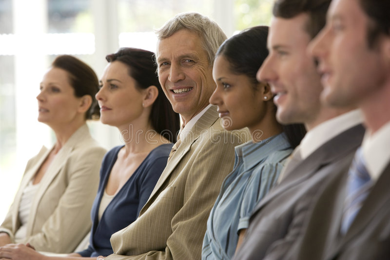 Confident mature businessman with team royalty free stock image