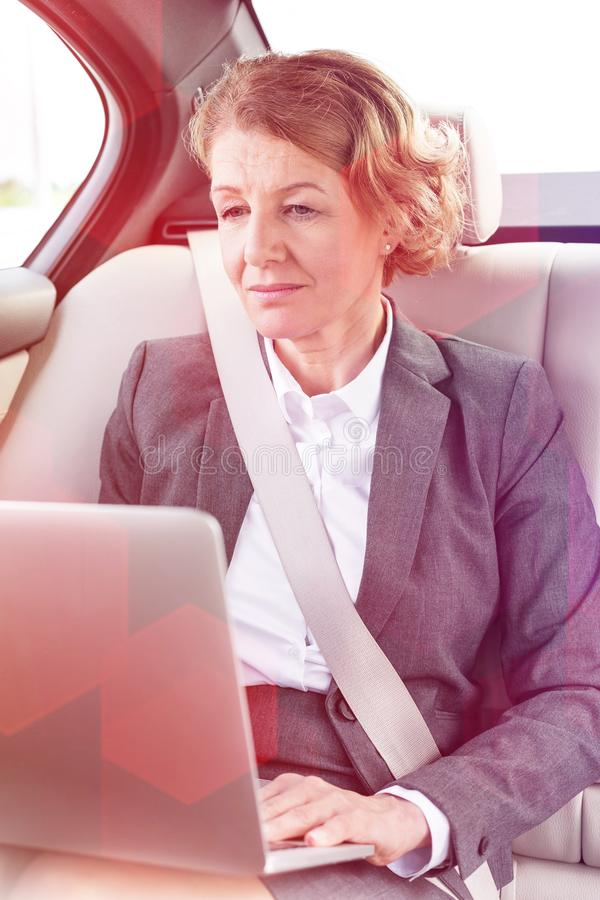 Confident mature businesswoman using laptop in car. Confident mature businesswoman using laptop stock photo