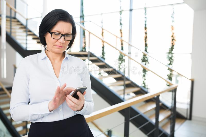 Businesswoman Using Smartphone While Standing In Office royalty free stock photo