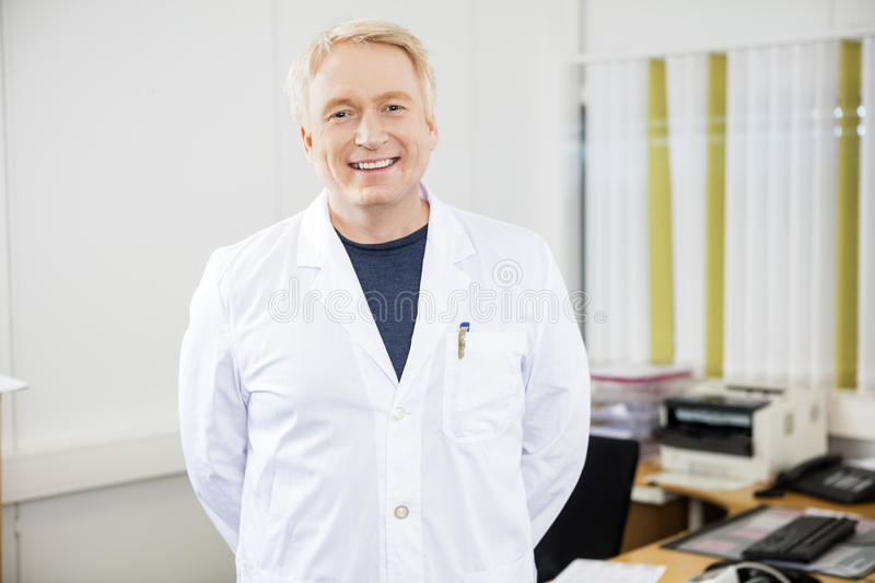 Confident Mature Doctor Smiling In Clinic stock image