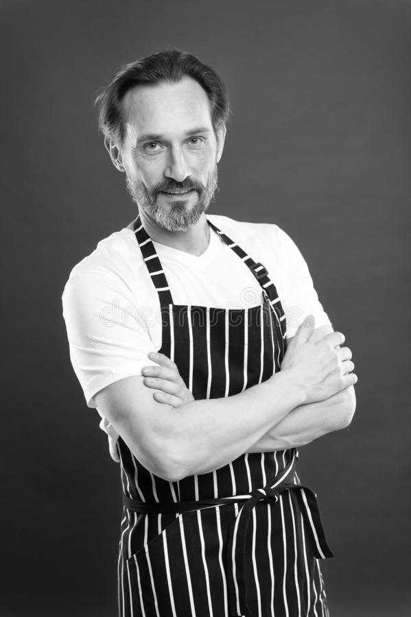Confident mature handsome man in apron red background. He might be baker gardener chef or cleaner. Good in everything. Multitasking and professional occupation royalty free stock image