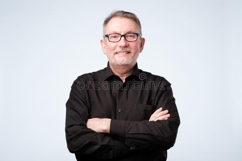 Confident mature man looking at camera and smiling while keeping arms crossed royalty free stock image