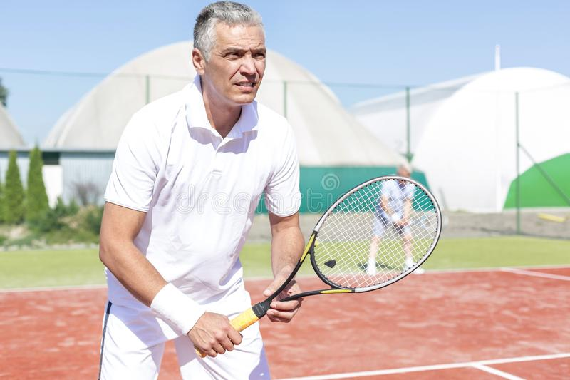 Confident mature man standing with tennis racket against friend playing doubles match on court. Confident mature men standing with tennis racket against friend royalty free stock photo