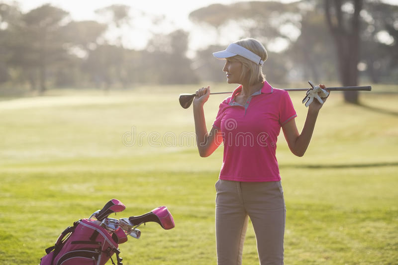 Confident mature woman carrying golf club royalty free stock photography