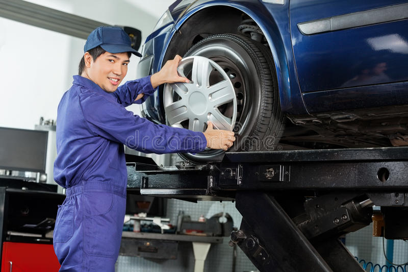 Confident Mechanic Fixing Hubcap To Car Tire. Side view portrait of confident mechanic fixing hubcap to car tire at garage stock image