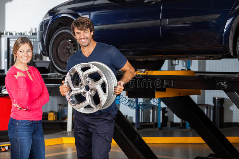 Confident Mechanic Holding Hubcap With Customer. Portrait of confident mechanic holding hubcap while standing with female customer at garage royalty free stock photos