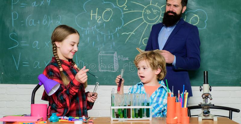 Confident medical experts. happy children teacher. doing experiments with liquids in chemistry lab. chemistry lab. back royalty free stock image