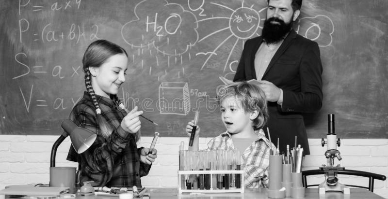 Confident medical experts. happy children teacher. doing experiments with liquids in chemistry lab. chemistry lab. back stock images