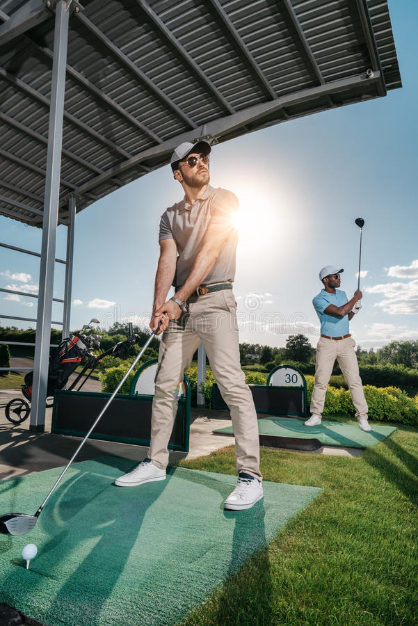 Confident men in sunglasses and caps playing golf stock photo