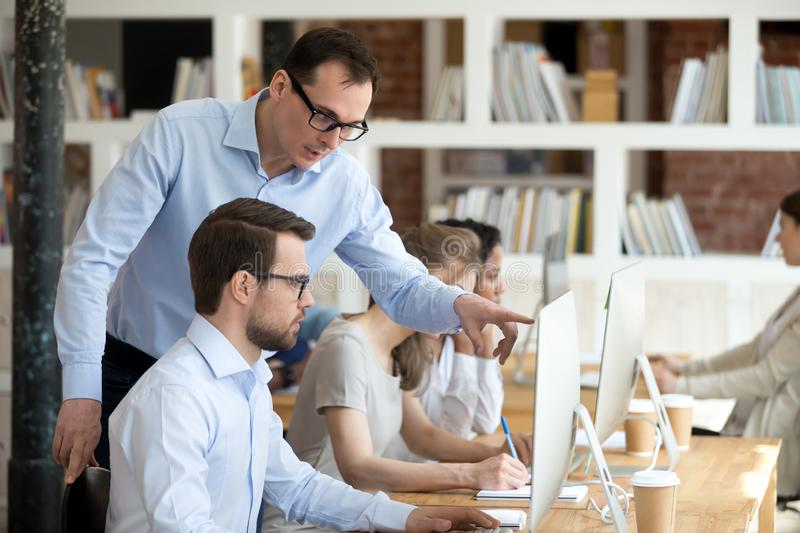 Confident mentor help trainee understand corporate program. Male colleagues discuss online project looking at pc screen working together in coworking space with stock photos