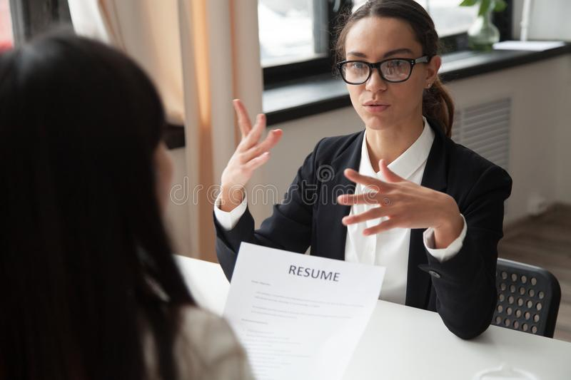 Confident millennial female applicant in glasses talking at job. Interview answering questions, vacancy candidate making first impression concept and royalty free stock photo
