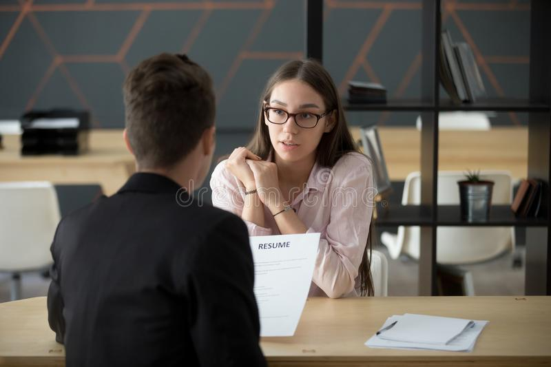 Confident millennial female applicant talking at job interview a. Nswering questions, young serious candidate speaking to hr telling about work experience royalty free stock images