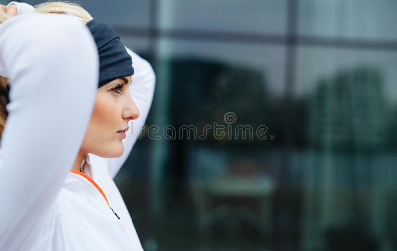 Confident and motivated fitness woman. Side view of attractive female athlete ready of a run in city. Confident and motivated fitness woman looking away royalty free stock images