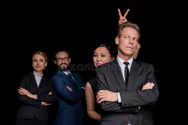 Multiethnic group of mature businesspeople standing with crossed arms and joking isolated on black stock photos