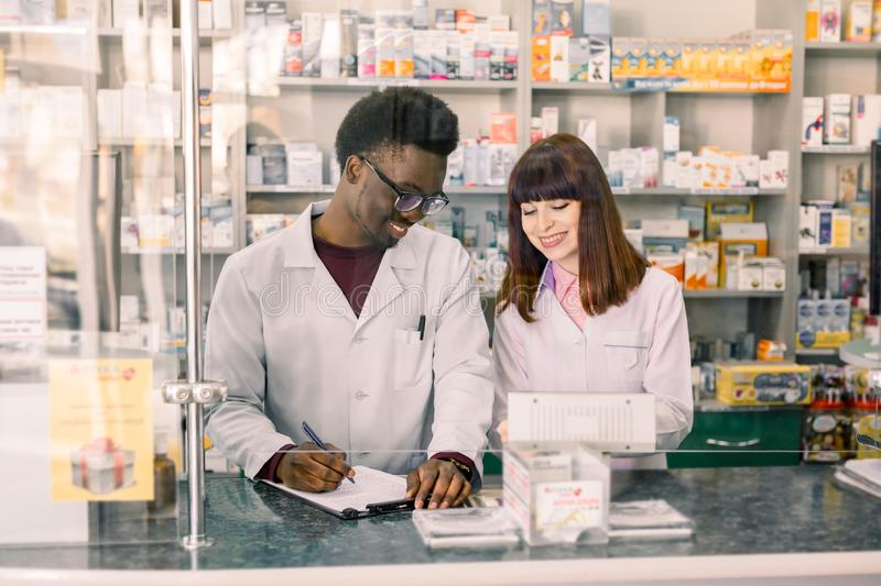 Confident multiethnical Male And Female Pharmacists In Pharmacy. African American man pharmacist making notes on stock photo