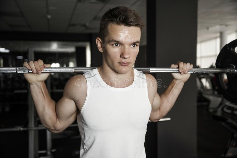 Confident muscular man trainings squats with barbells overhead in gym.  royalty free stock photography