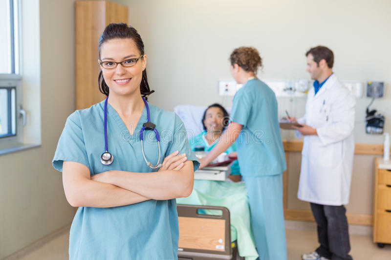 Confident Nurse Against Patient And Medical Team royalty free stock photography