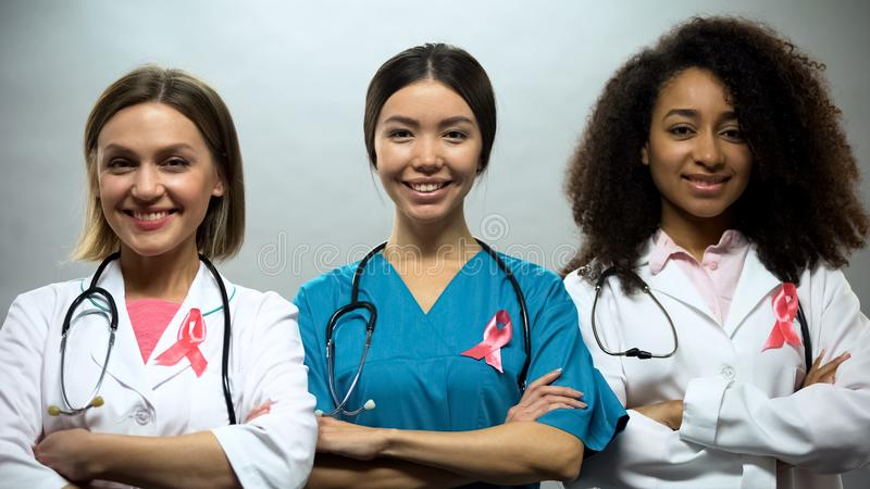 Confident nurses with pink ribbons smiling into camera, breast cancer awareness stock photos