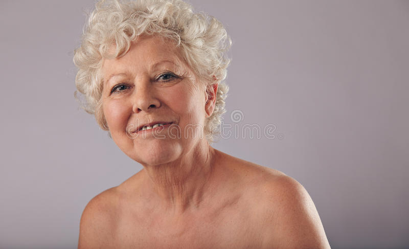 Confident old woman with smile on her face stock image