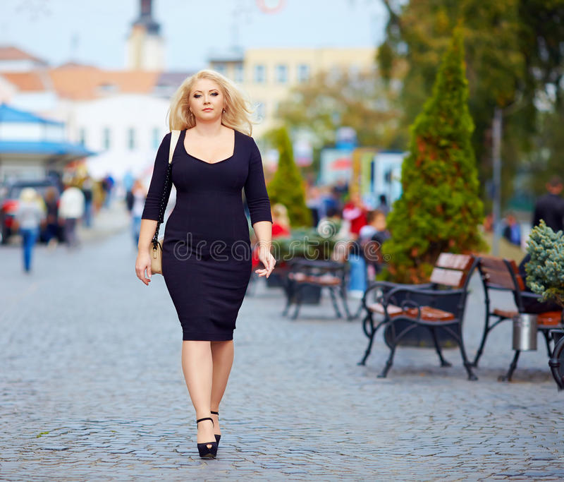 Confident overweight woman walking the city street. Confident overweight woman walking alone the city street royalty free stock photography