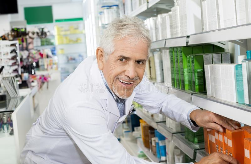 Confident Pharmacist Arranging Medicines On Shelf In Pharmacy. Side view portrait of confident senior male pharmacist arranging medicines on shelf in pharmacy royalty free stock image