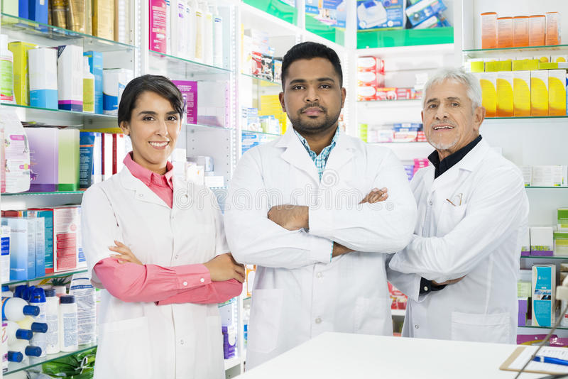 Confident Pharmacists Standing Arms Crossed In Pharmacy royalty free stock images