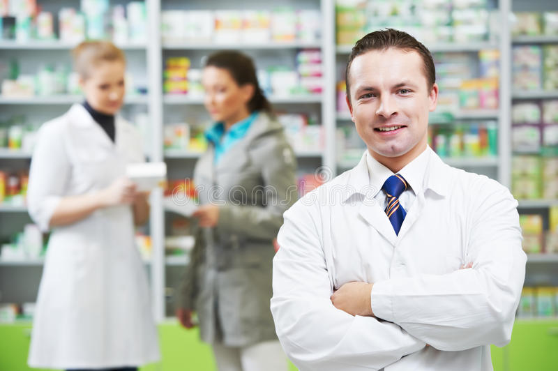 Confident pharmacy chemist man in drugstore royalty free stock images