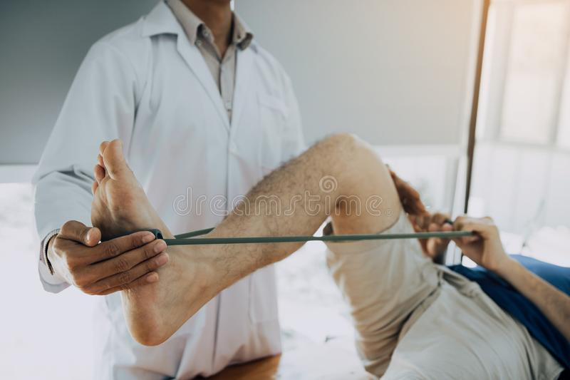 Confident physical therapist helps patient use resistance band stretching out his leg in clinic room stock photography
