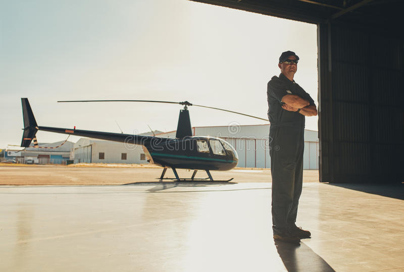 Confident pilot standing in airplane hangar royalty free stock photo