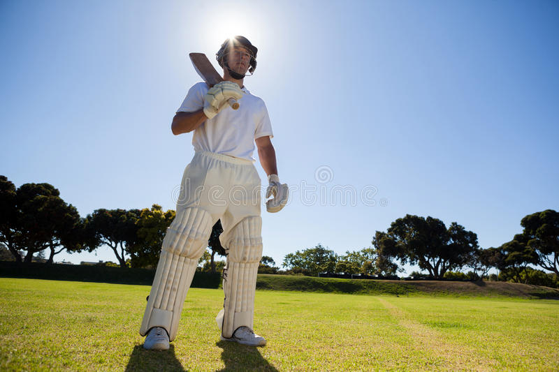 Confident player with cricket bat standing against sky. Low angle view of confident player with cricket bat standing against blue sky stock photography