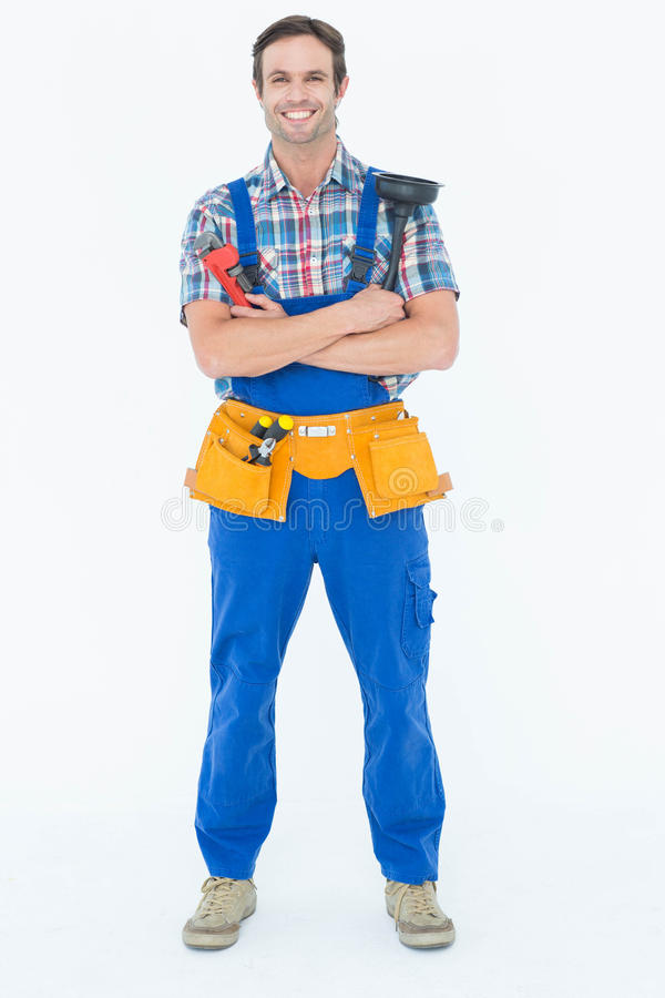 Confident plumber holding monkey wrench and plunger. Full length portrait of confident plumber holding monkey wrench and plunger over white background stock photography