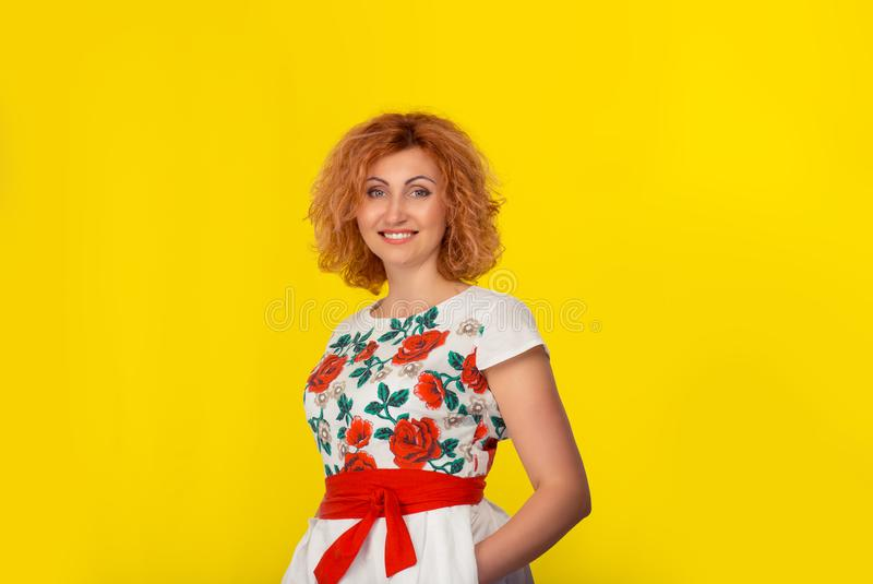 Happy woman with arms folded standing looking at camera smiling stock photography
