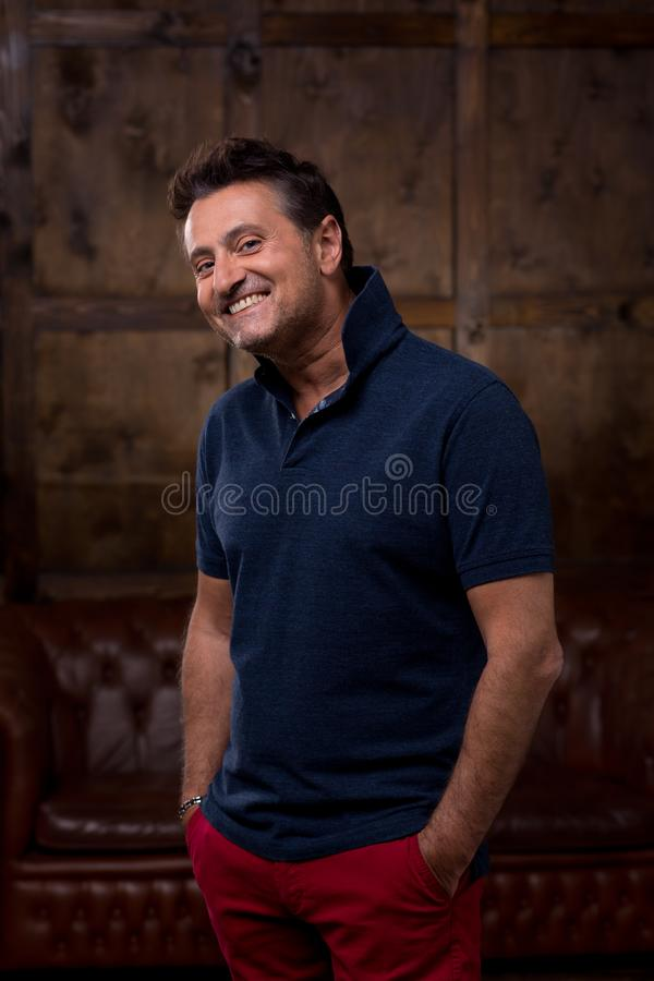 Confident positive relaxed man in casual clothes standing alone and putting two hands into the pockets while looking curiously at stock image
