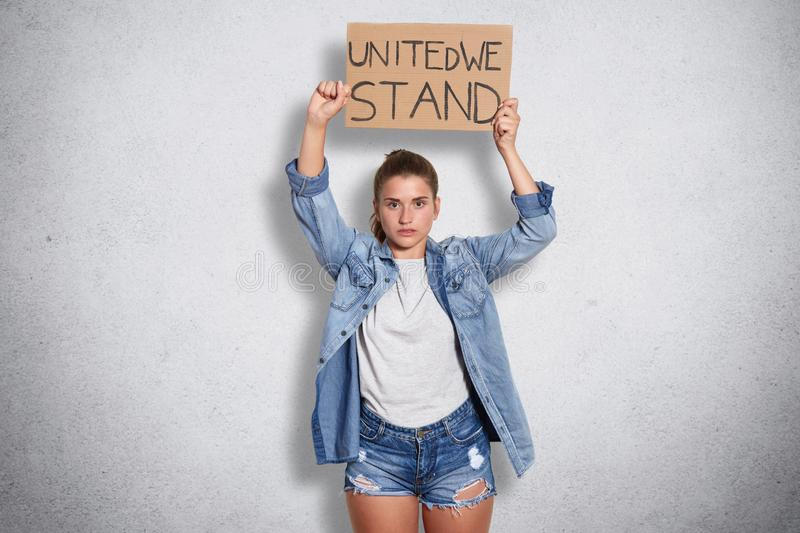 Confident powerful brunette female wearing jeans jacket, shorts, casual white t shirt, holding feminist inscription above her head. Having serious facial royalty free stock images