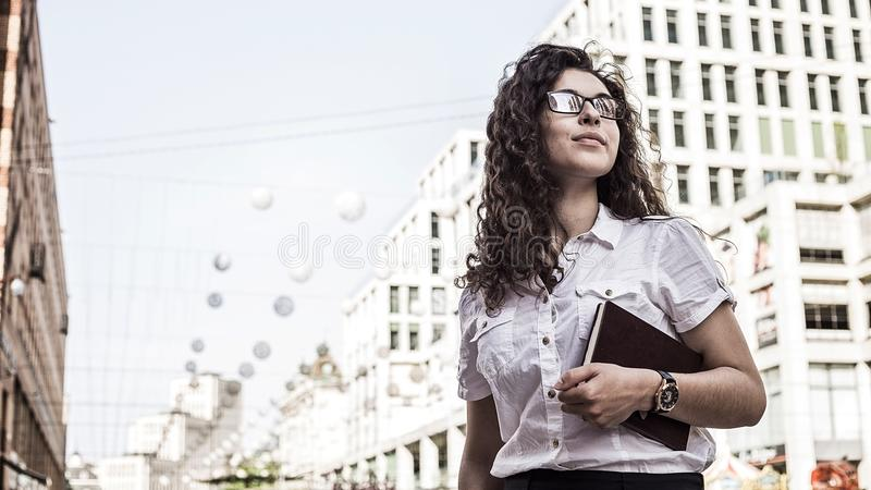 Confident and pretty young woman with black curly hair standing on the buildings background stock photo