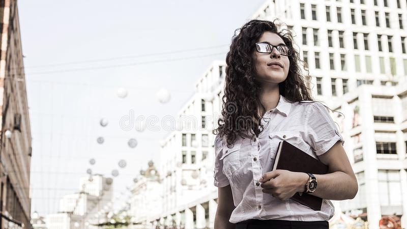 Confident and pretty young woman with black curly hair standing on the buildings background stock photos