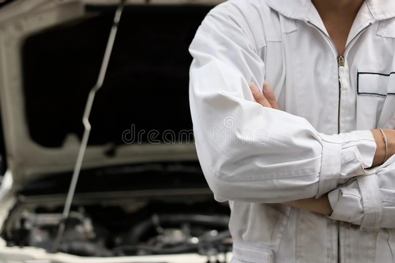 Confident professional mechanic in uniform crossing one`s arms with hood at repair garage. Car insurance concept. Confident professional mechanic in uniform royalty free stock photo