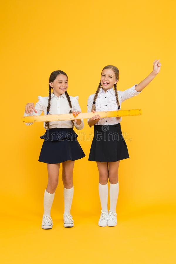 Confident pupils. happy small girls study mathematics. students use yellow ruler. stem disciplines. back to school. Maths and geometry. Kids in uniform stock images