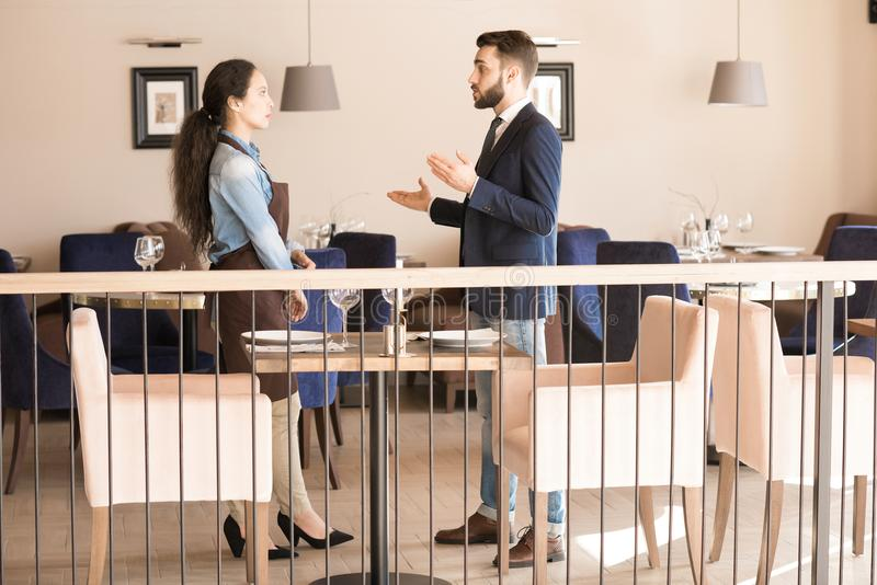 Confident restaurant manager explaining tasks to waitress. Confident qualified male restaurant manager working with staff personnel: successful men explaining royalty free stock images