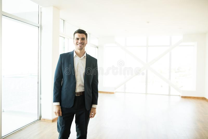 Confident Real Estate Agent Smiling In New Luxury Home stock image