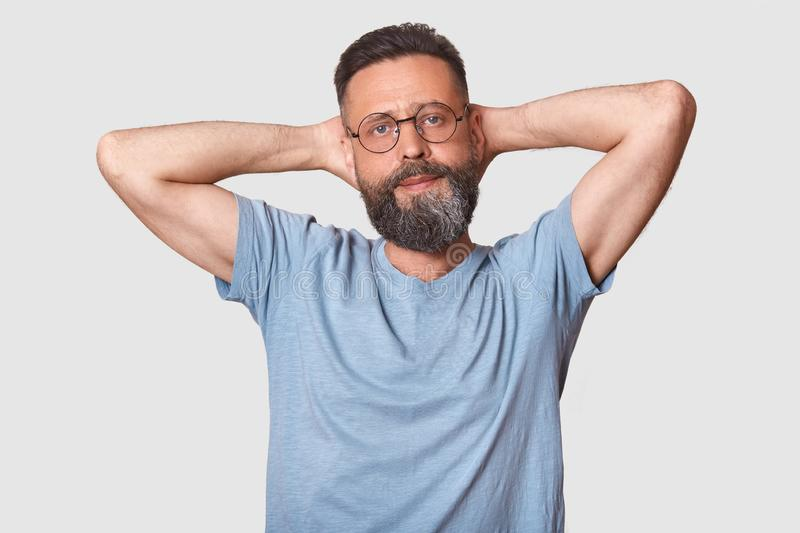 Confident relaxed calm man rises his arms, touching his head with both hands, having time for rest, looks quiet and peaceful. stock photo