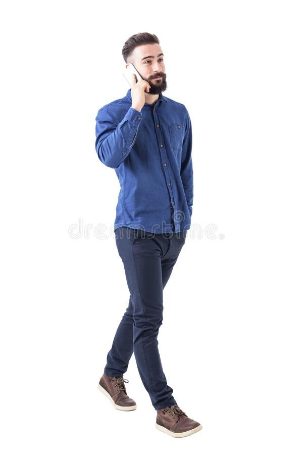 Confident relaxed young adult male business manager walking and talking on the mobile phone. royalty free stock photo
