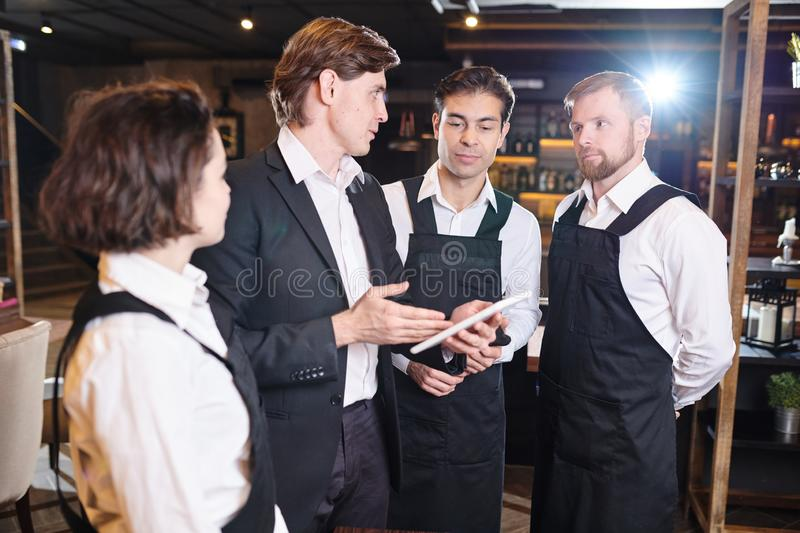 Confident restaurant manager discussing seating chart with waite stock photography