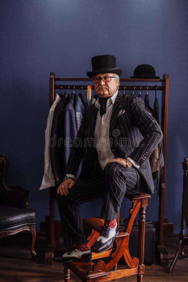 Confident retro style fashion man sitting on wooden stool tailor`s workshop royalty free stock image