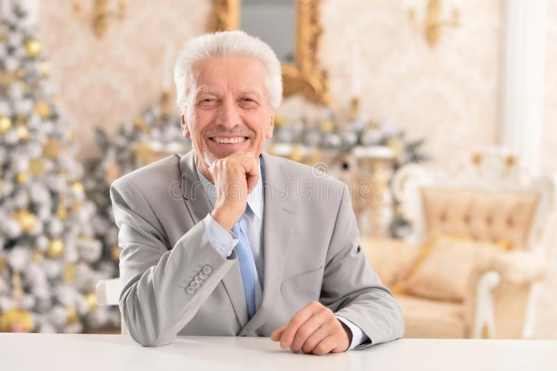 Confident senior businessman sitting at table at home stock images
