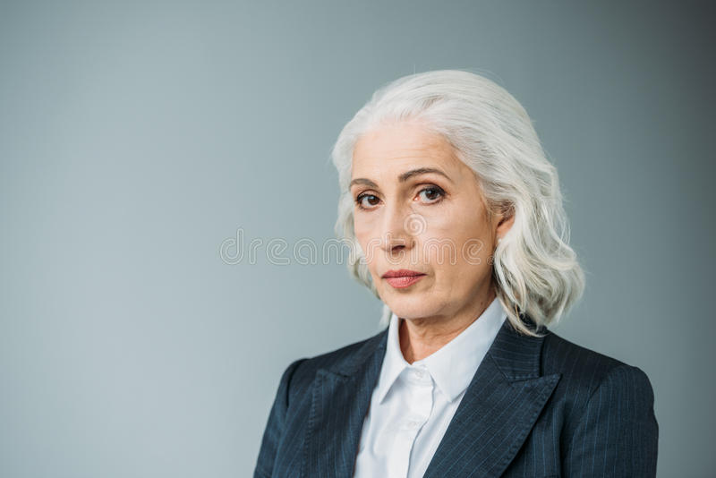 Confident senior businesswoman in suit on grey. Portrait of confident senior businesswoman in suit on grey royalty free stock image